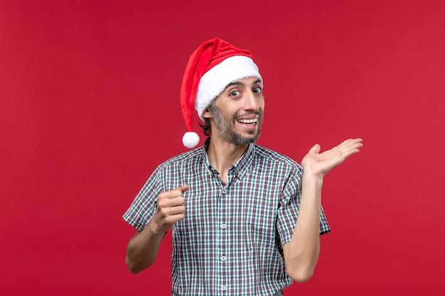 Vista frontal joven con expresión emocionada en la pared roja vacaciones año nuevo rojo masculino