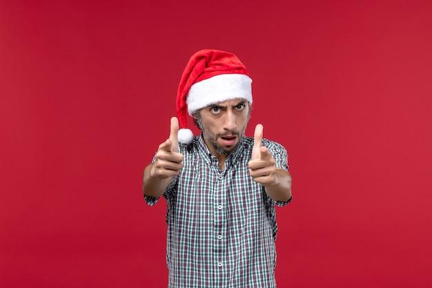 Vista frontal joven con expresión enojada en la pared roja vacaciones rojo año nuevo macho