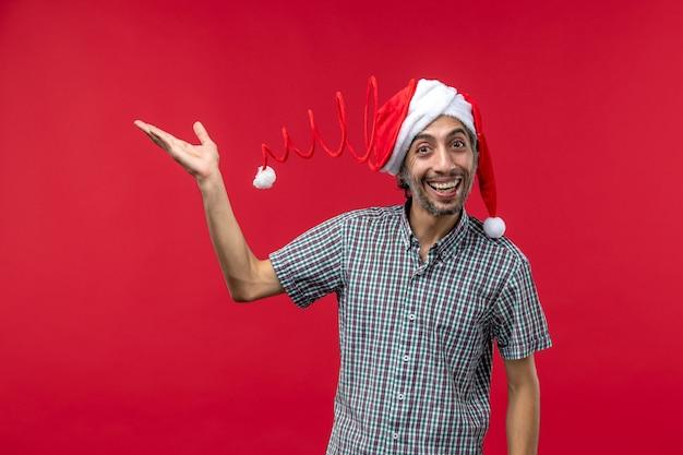 Vista frontal del joven con expresión feliz en la pared roja