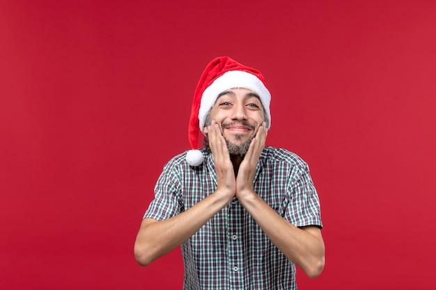 Vista frontal joven con expresión linda en pared roja vacaciones año nuevo rojo