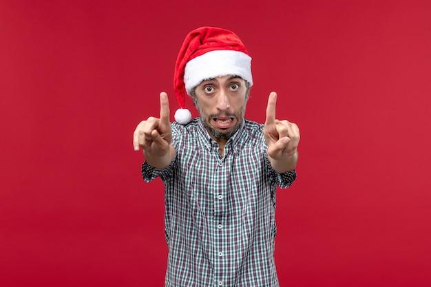 Vista frontal joven con expresión nerviosa en la pared roja vacaciones año nuevo rojo masculino