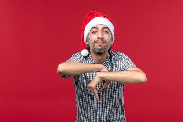 Vista frontal joven con expresión tranquila en la pared roja vacaciones año nuevo rojo