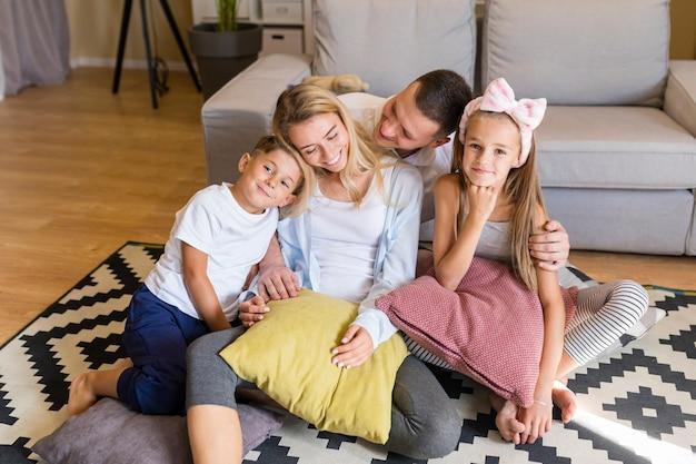 Vista frontal joven familia pasar tiempo en la sala de estar