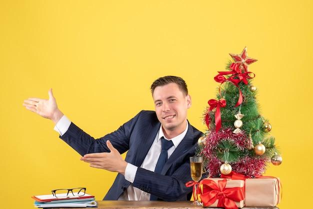 Vista frontal del joven feliz apuntando a algo sentado en la mesa cerca del árbol de navidad y regalos en amarillo