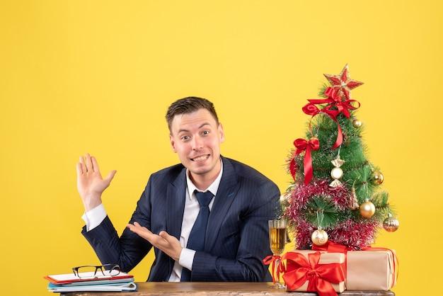 Vista frontal del joven feliz apuntando. fondo sentado en la mesa cerca del árbol de navidad y regalos en amarillo