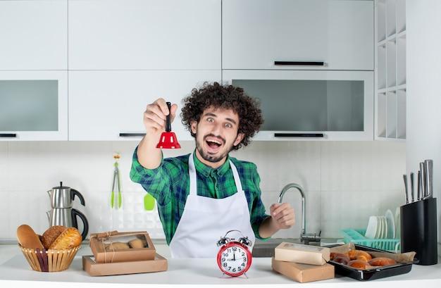 Vista frontal del joven feliz de pie detrás de la mesa varios pasteles y mostrando la campana del anillo rojo en la cocina blanca