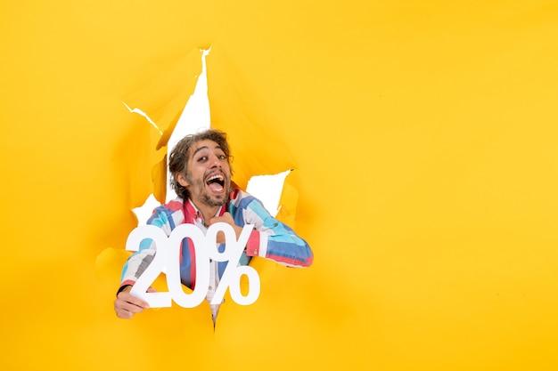 Vista frontal del joven feliz que muestra el veinte por ciento en un agujero rasgado en papel amarillo