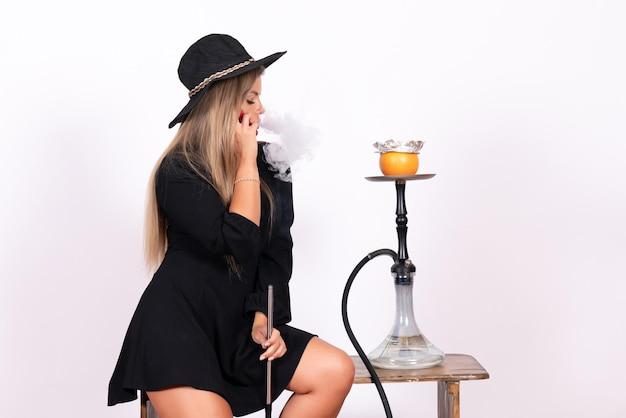 Vista frontal del joven fumar narguile en la pared blanca