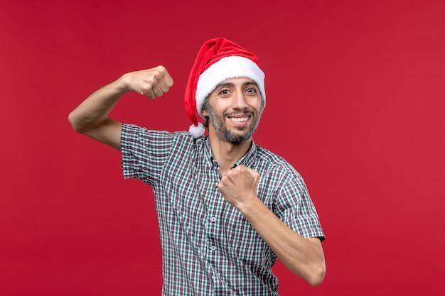 Vista frontal joven con gorro de año nuevo en la pared roja macho de vacaciones de año nuevo rojo