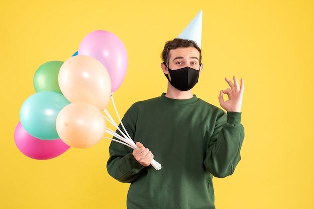 Vista frontal joven con gorro de fiesta y globos de colores haciendo cartel okey de pie en amarillo