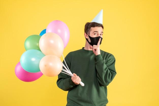 Vista frontal joven con gorro de fiesta y globos de colores haciendo cartel de shh de pie en amarillo