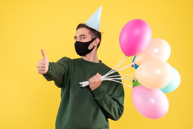 Vista frontal joven con gorro de fiesta y globos de colores haciendo pulgar arriba cartel de pie en amarillo