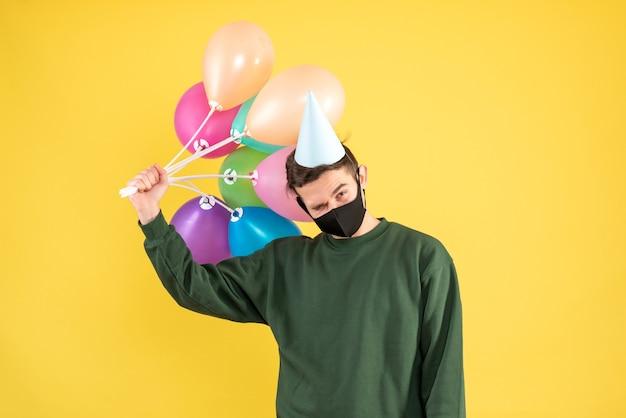 Vista frontal joven con gorro de fiesta sosteniendo globos de colores de pie sobre fondo amarillo
