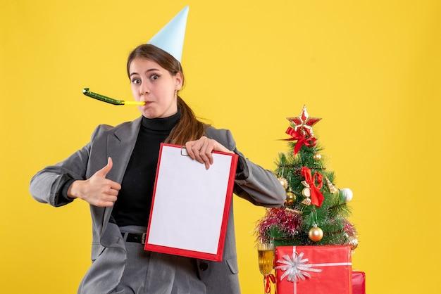 Vista frontal joven con gorro de fiesta usando matraca sosteniendo documentos haciendo pulgar arriba cartel de pie cerca del árbol de navidad y cóctel de regalos