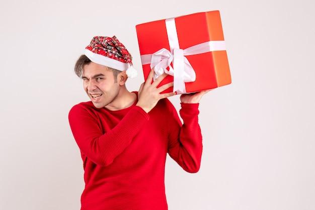 Vista frontal joven con gorro de papá noel con regalo sobre fondo blanco.