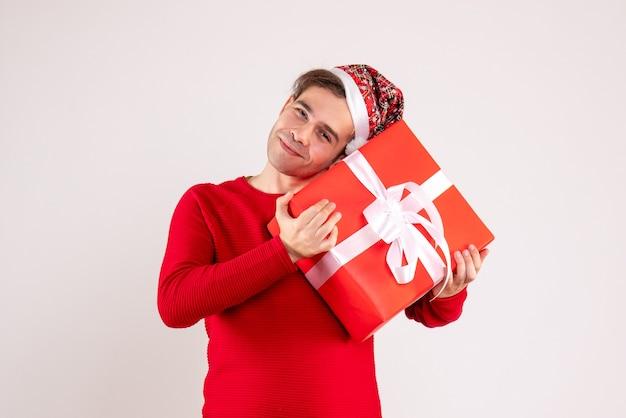 Vista frontal joven con gorro de papá noel sosteniendo el regalo firmemente sobre fondo blanco.