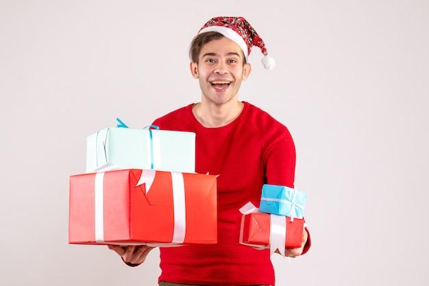 Vista frontal joven con gorro de papá noel sosteniendo regalos sobre fondo blanco.
