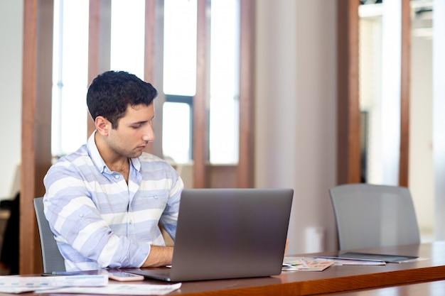 Una vista frontal joven guapo con camisa a rayas trabajando dentro de su oficina usando su computadora portátil plateada durante el edificio durante la actividad laboral diurna
