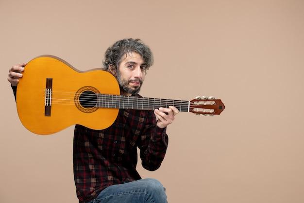 Vista frontal joven con guitarra sobre fondo rosa músico de concierto actuación en vivo tocar colores de banda