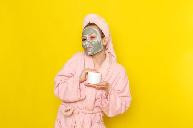 Una vista frontal joven hermosa mujer en bata de baño rosa con crema