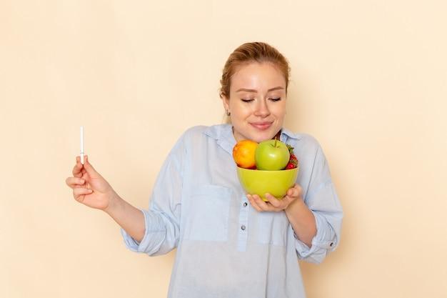 Vista frontal joven hermosa mujer en camisa sosteniendo un plato con frutas y oliendo su aroma en la pose de mujer modelo de fruta de pared crema clara