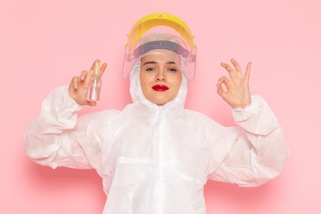 Vista frontal joven hermosa mujer en traje blanco especial con casco protector sosteniendo spray con sonrisa en el espacio rosa traje especial niña mujer
