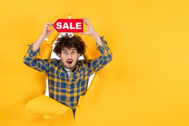 Vista frontal joven hombre sosteniendo venta rojo escrito sobre fondo amarillo rasgado