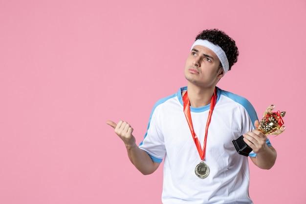 Vista frontal joven jugador en ropa deportiva con copa de oro en pared rosa