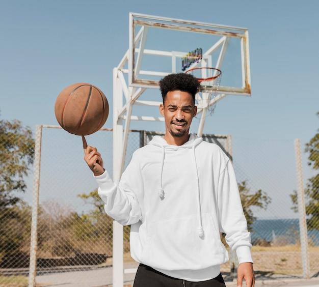 Vista frontal joven jugando baloncesto al aire libre