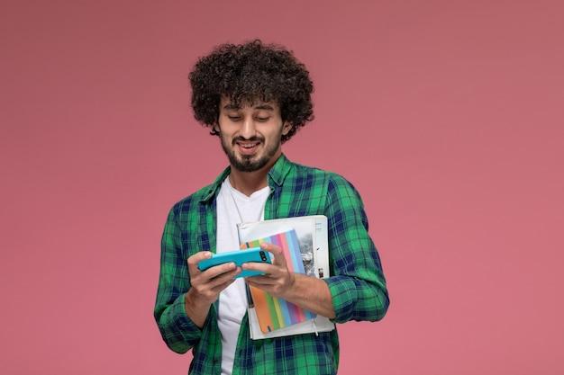 Vista frontal joven jugando juegos de carreras y sosteniendo libros