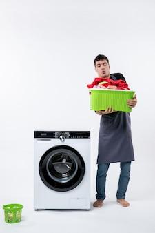 Vista frontal del joven con lavadora y ropa sucia dentro de la canasta en la pared blanca