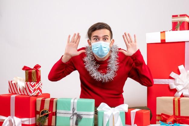 Vista frontal joven con máscara abriendo las manos sentados alrededor de regalos de navidad