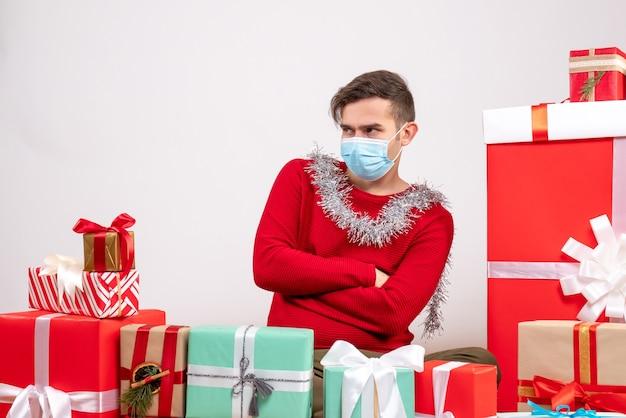 Vista frontal joven con máscara cruzando las manos sentado alrededor de regalos de navidad