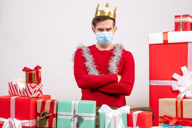Vista frontal joven con máscara cruzando las manos sentado en el piso regalos de navidad