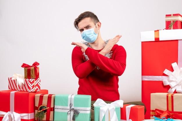 Vista frontal joven con máscara cruzando las manos sentados alrededor de regalos de navidad