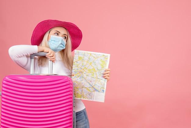 Vista frontal joven en máscara médica de pie cerca de la maleta con mapa