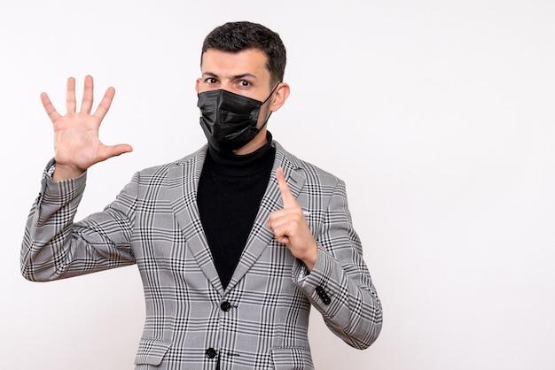 Vista frontal joven con máscara negra dando cinco de pie sobre fondo blanco aislado