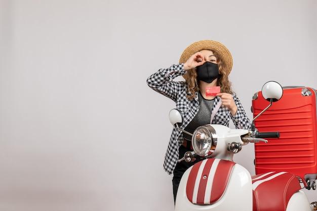 Vista frontal joven con máscara negra sosteniendo boleto haciendo binoculares de mano de pie cerca de ciclomotor rojo