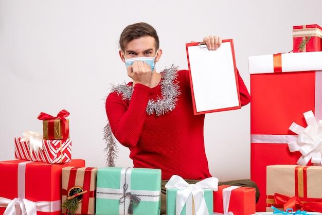 Vista frontal joven con máscara poniendo la mano a la boca sentado alrededor de regalos de navidad