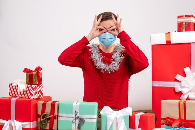 Vista frontal joven con máscara poniendo manos binoculares a los ojos sentado alrededor de regalos de navidad