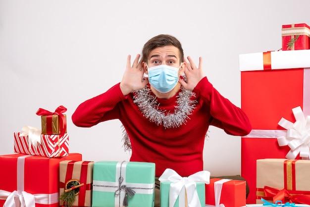 Vista frontal joven con máscara poniendo las manos en los oídos escuchando algo sentado alrededor de los regalos de navidad