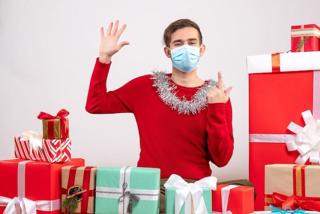 Vista frontal joven con máscara poniendo su mano sentado alrededor de regalos de navidad