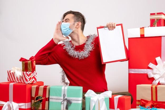 Vista frontal joven con máscara saludando a alguien sentado alrededor de regalos de navidad