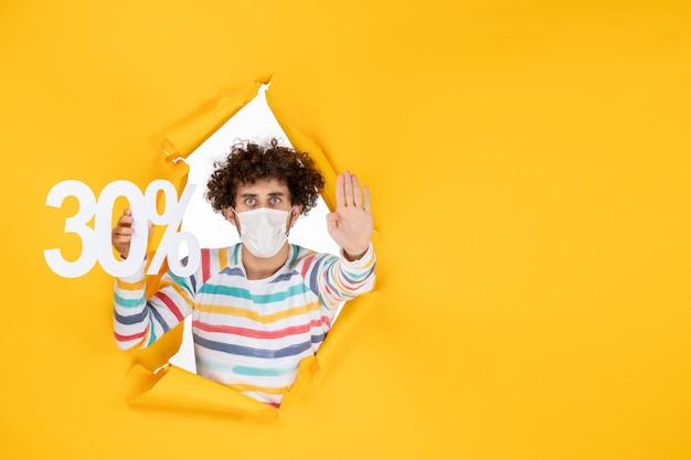 Vista frontal joven en máscara sosteniendo en amarillo comercial salud covid- foto virus pandémico