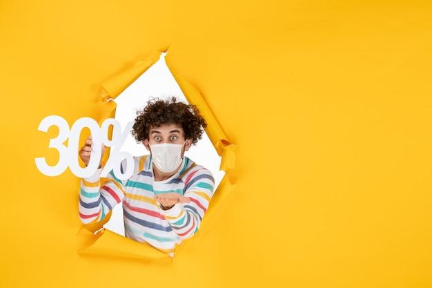 Vista frontal joven en máscara sosteniendo en color amarillo compras salud covid- foto venta de virus pandémico