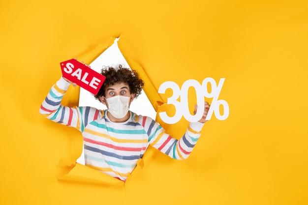 Vista frontal joven en máscara sosteniendo en color amarillo pandémico compras venta de virus covid de salud roja