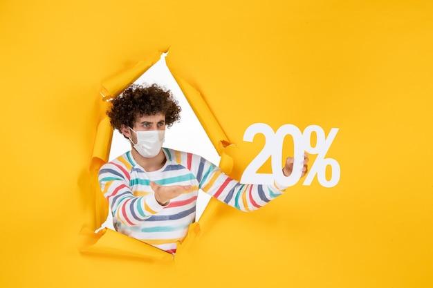 Vista frontal joven con máscara sosteniendo la escritura en amarillo venta coronavirus salud covid- foto en color pandemia