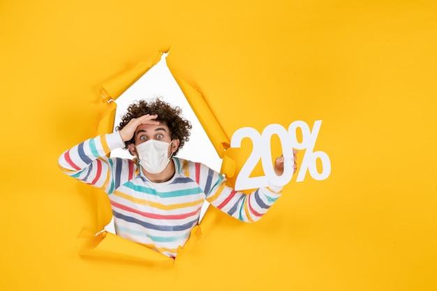 Vista frontal joven con máscara sosteniendo la escritura en la venta amarilla coronavirus salud pandémica covid- foto en color