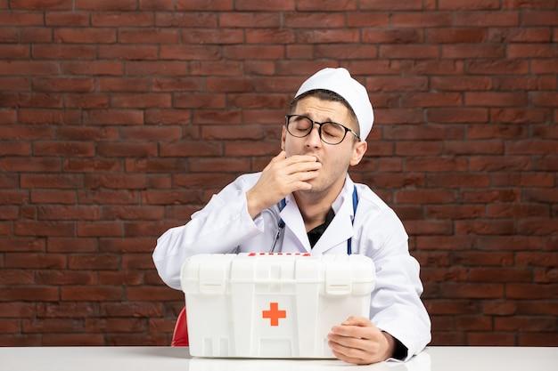 Vista frontal joven médico bostezo en traje médico blanco con botiquín de primeros auxilios en la pared de ladrillo marrón
