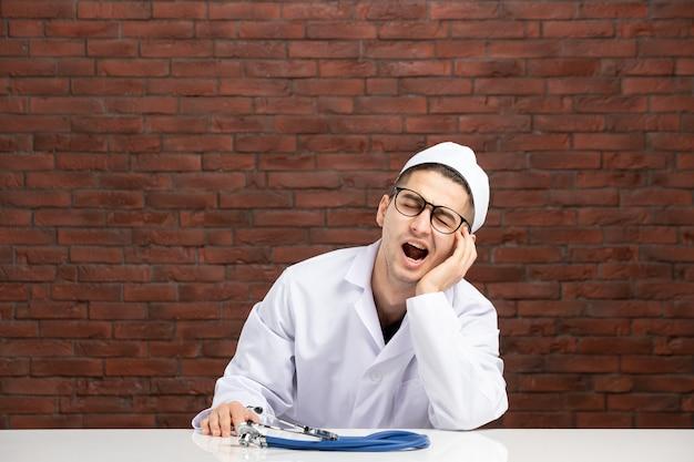 Vista frontal joven médico cansado en traje médico blanco sobre pared de ladrillo marrón